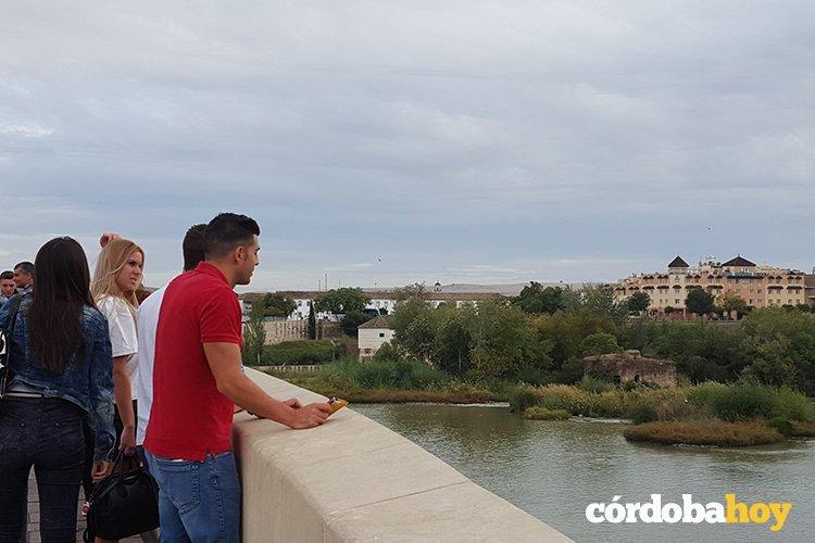 Turistas contemplando el Guadalquivir desde el Puente Romano